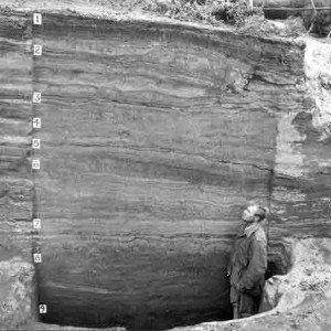 """Dr. Lewis Giddings standing in front of the nine """"stratified occupational layers"""" at the Onion Portage, excavation in 1961. Photo Credit: Doug Anderson"""